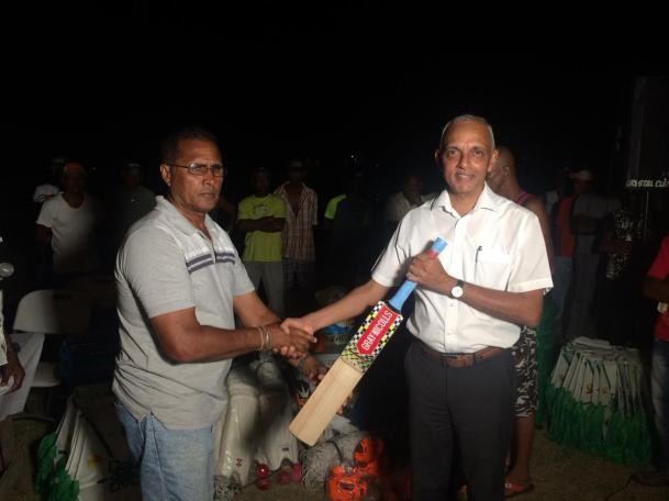 Minister of Communities, Ronald Bulkan handing over the sport gear to President of the Crabwood Creek community ground, Dennis DeAndrade.