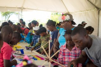 Minister within the Ministry of Natural Resources, Simona Broomes with several children making kites.