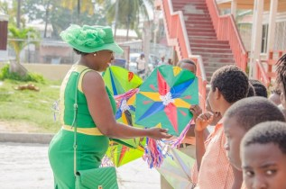 Minister of Education, Dr. Nicolette Henry shares kites to the students of Enterprise Primary School.