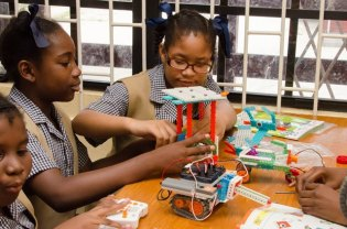 Students of St. Pius Primary School using the materials from donated Robotics Kits.