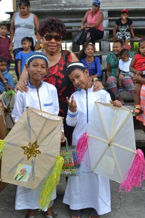 Children posing with Minister of Social Protection, Amna Ally after receiving their kites.