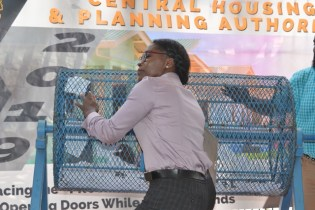 A Central Housing and Planning Authority (CH&PA) staffer pulls the winning lottery ticket.