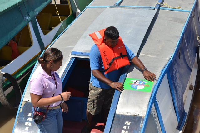 Public Communications Officer observing a boat operator place the MARAD sticker on his boat at the Parika Stelling.