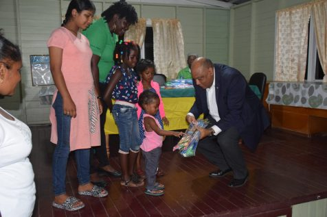 Minister of Natural Resources, Raphael Trotman presents a little one with a kite