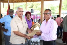 Minister of Agriculture, Noel Holder presents a lease to a resident who applied