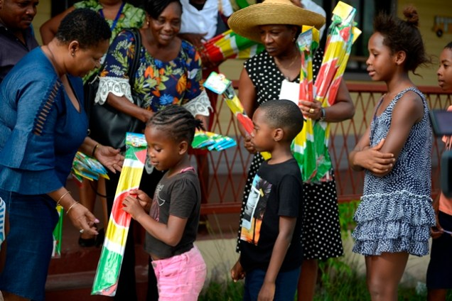 Minister of Public Health, Volda Lawrence distributing kites to the children of East La-Penitence and Stevedore Housing Scheme.