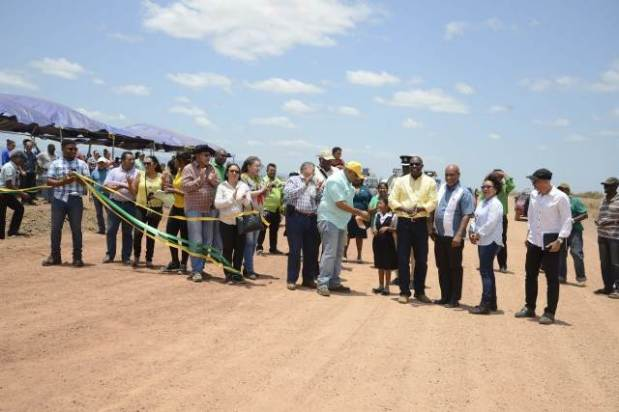 Ministers Trotman and Patterson cut the ribbon to mark the official opening of the Manari bypass. Malicha Cumberbatch [standing between the ministers] from Arapaima Primary School who helped to cut the ribbon.