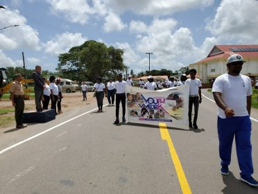 Minister of Social Cohesion, with responsibility for Culture, Youth and Sport, Dr. George Norton being saluted during a march pass.