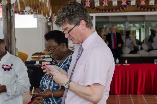 [In the photo, from right to left] British High Commissioner, Greg Quinn and Vice Principal, Myrna Lee tasting some of the cuisines on display at the tea party hosted at the British High Commissioner's residence.
