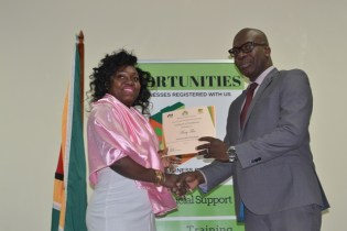 Mary Flue receiving her certificate from the Coordinator of the Citizens Security Strengthening Programme (CSSP), Dr. Clement Henry.