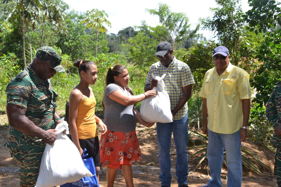 Bridget De Silva and her daughter Mary Ann Frasier accept a relief hamper from Ministers David Patterson and Raphael Trotman in Mahdia. Also in picture is Capt. Michael Andrews from the CDC