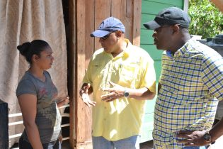 Ministers Patterson and Trotman speak with Mahdia resident, Sadia Boodram before presenting her with a relief hamper