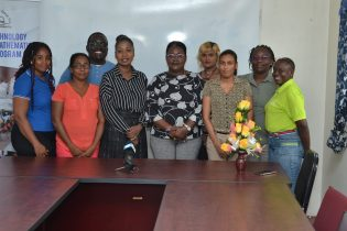 Minister Simona Broomes pose with staff members and volunteers of the Volunteer Youth Corps during a visit earlier today