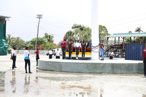Youths being thought to raise the National Flag by members of the Guyana Defence Force.