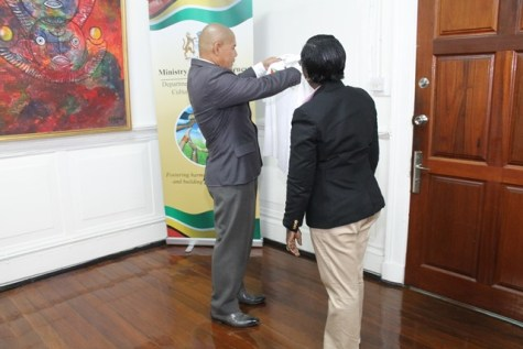 Hon. Minister of Social Cohesion, Dr. George Norton taking a closer look at the shirt presented to him.