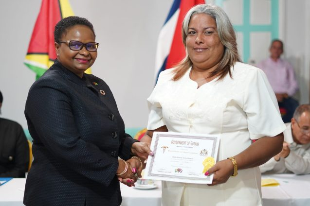 Minister of Public Health Volda Lawrence hands over a certificate to one of the doctors
