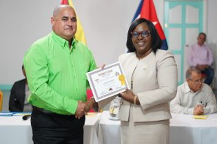 Minister within the Ministry of Public Health, Dr. Karen Cummings presents a certificate to one of the doctors