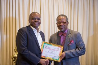 A member from ExxonMobil receiving an award for implemented Occupational Safety measures.