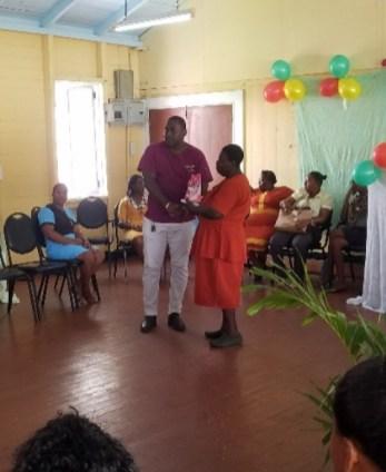 Regional Health Officer (RHO) Dr. Cedel Mc Watt presenting a token of appreciation to a working mother from the West Demerara Regional Hospital.
