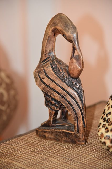 A sculpted Sankofa bird, native to Ghana. The mythical bird's feet are firmly planted forward with its head turned backwards.