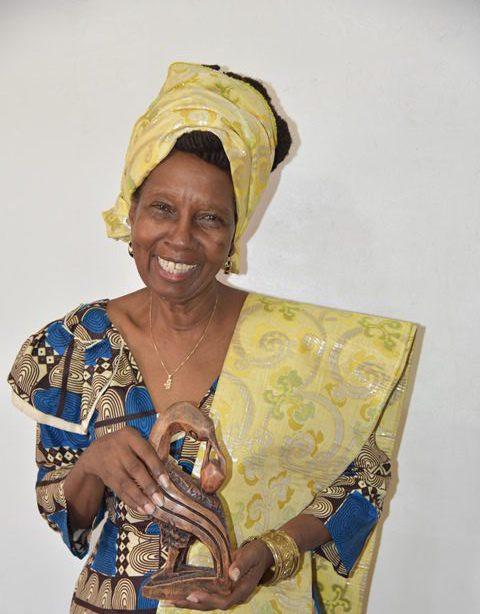 Penda Guyan, President of the Ghana Day Organising Committee, holds a sculpted Sankofa bird.