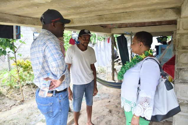Minister of Public Infrastructure, David Patterson and Minister of Public Health, Volda Lawrence interact with a resident during a community walkabout