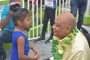 Minister of Natural Resources, Raphael Trotman interacts with a little girl during his walkabout the community of Zeelandia, Wakenaam