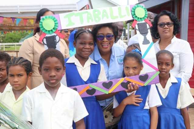 Minister of Telecommunications, Catherine Hughes is welcomed by students in the Itabili community on Wednesday.