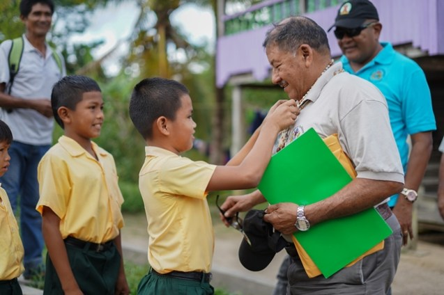 Minister of Indigenous Peoples' Affairs, Sydney Allicock being welcomed by a student of the Sebai Primary School.