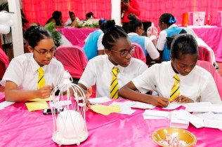 Students of the Queen's College team preparing their rebuttal (Ministry of Education photo)