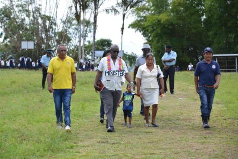 Minister Winston Felix is accompanied by representatives of Kartabo during his visit to the Region Seven community.