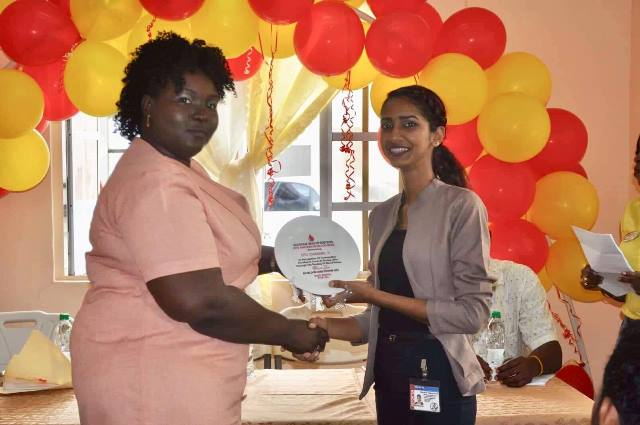 Medical Superintendent of the New Amsterdam Hospital hands over an award to a staff of Dave's Television Station (DTV) Nareema Ali. The TV station was recognised for regularly hosting blood drives.