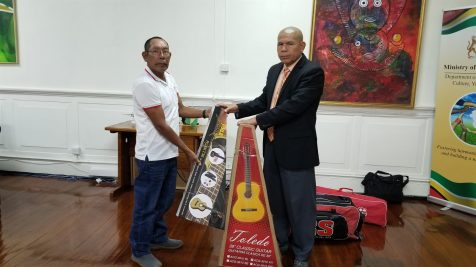 Minister Norton hands over two guitars to Sestus Williams. The instruments will serve the community of Haimaracabra, which is the satellite area for Waramuri, located in Region One.