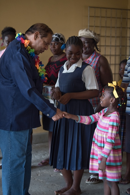 Prime Minister, Moses Nagamootoo greets a child as he arrived at Golden Grove Primary School.