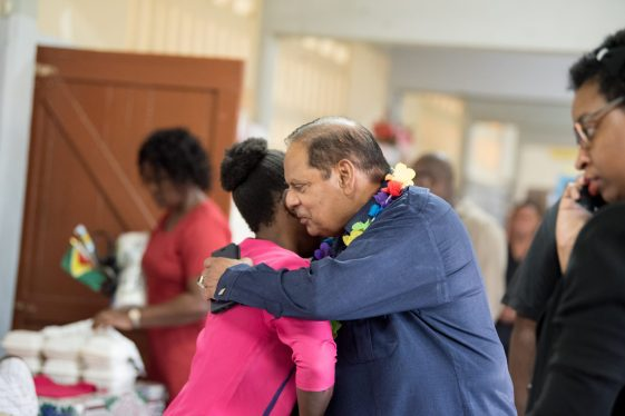 Prime Minister, Moses Nagamootoo embraces a young resident of Golden Grove at a community meeting held in the area