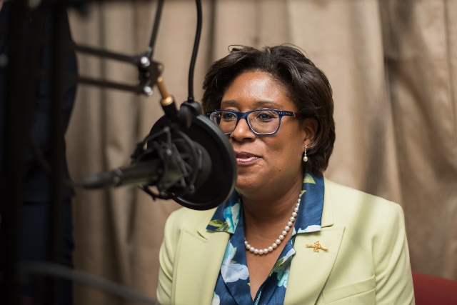 Minister of Public Telecommunications, Hon. Catherine Hughes tests the equipment at the official launch of the University of Guyana's '95.5 Intelligent FM' radio station.