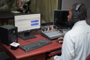 A peek inside the radio station; an operator at the controls.