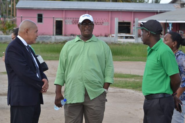 Minister of Social Cohesion, Hon. Dr. George Norton along with his technical team speaking with Fitzroy Fredericks, President of the Queenstown Development Association.