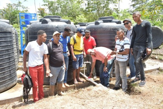 GWI's Managing Director turn on the valve to release water into the community to commence the testing phase.