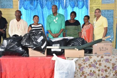 Minister of Business, Haimraj Rajkumar and with Director-General of the Ministry of the Presidency, Joseph Harmon along with residents of Martindale as they h and over the gifts