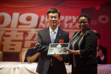 Hon. Volda Lawrence, Minister of Public Health presents a plaque to the Head of the 14th. Chinese brigade Dr. Shen Jiansong.