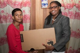 Young Pawan Etwaroo, Region 6 National Grade Six Assessment (NGSA) top student receives a laptop from Minister of Public Service, Tabitha Sarabo-Halley.