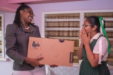 Eleven-year-old Chitra Ramdihal of Cropper Primary happily accepts laptop from Minister of Public Service, Tabitha Sarabo-Halley.