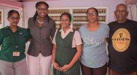 Minister of Public Service, Tabitha Sarabo-Halley with eleven-year-old Chitra Ramdiha with her family members.