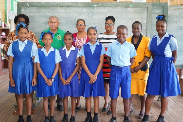 Minister of Social Cohesion, with responsibility for Culture, Youth and Sport, Dr. George Norton with the top students and teachers of the Howell Wilson Primary School.