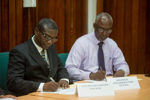 Head of the Guyana Securities Council, Rawle Lucas signs his MOU.