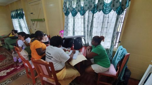 Michelle Biswah in green seated at the table with the GECOM enumerator and APNU+AFC scrutineer during her registration process.