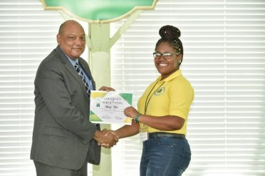 Minister of Natural Resources, Mr. Raphael Trotman presents a certificate of participation to Ms. Melody Miller.