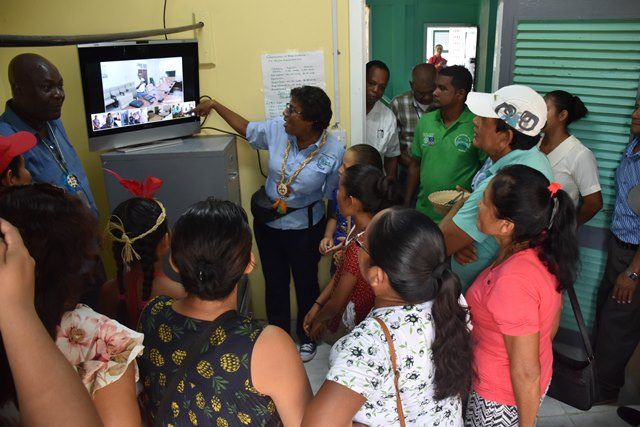 Minister of Public Telecommunications, Catherine Hughes explains how the video-conferencing equipment works to residents of Orealla in Region six.