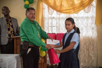 Minister of Indigenous Peoples' Affairs, Hon. Sydney Allicock presents an award to the region's top student 11-year-old Alana Lewis